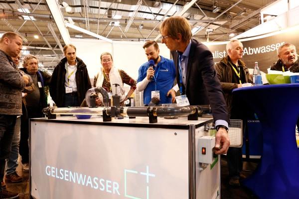 Erfinder Rüdiger Szymczak (r.) erklärt auf der InfraTech am MOdell, wie die Schirmspülung funktioniert.